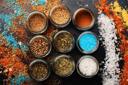 Set of spices on dark grey background. Glass jars