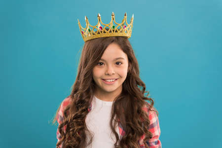 Kid wear golden crown symbol of princess. Girl cute baby wear crown while stand blue background. Become princess concept. Every girl dreaming to be princess. Lady little princess. Dreams come true Stockfoto