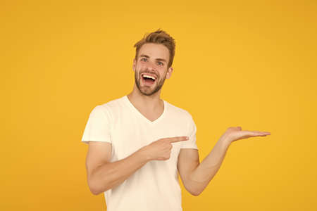 Man cheerful face show something copy space. Promoting product for men. Launching product. Guy recommend product. Commercial advertisement. Promotion concept. Check it out. Product presentation Archivio Fotografico
