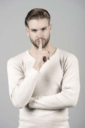 Keep silence. Man handsome attractive silence gesture. You better keep our secret. Being entrusted with secret can be both delight and burden. Guy asks to keep his secret