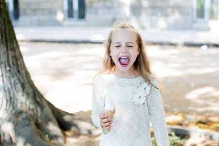 It is too cold. Girl sweet tooth eat ice cream. Kid shouting emotional face with ice cream. Child white ice cream in waffle cone. Summer treats concept. Happy childhood. Buy ice cream street food