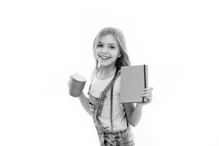 Girl cute child long hair drink cocoa or tea. Schoolgirl with book or notepad and mug having tea break. Water balance concept. Enjoying tea before school classes. Relax and recharge. Inspiring drink