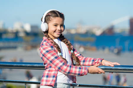 Make your kid happy with best rated kids headphones available right now. Girl child listen music outdoors with modern headphones. Kids headphones tested and ranked best to worst. Enjoy sound