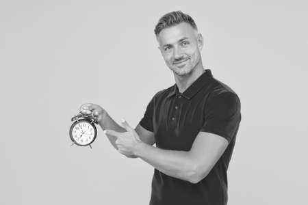 Handsome caucasian guy point finger at mechanical alarm clock showing urgent time yellow background, deadline