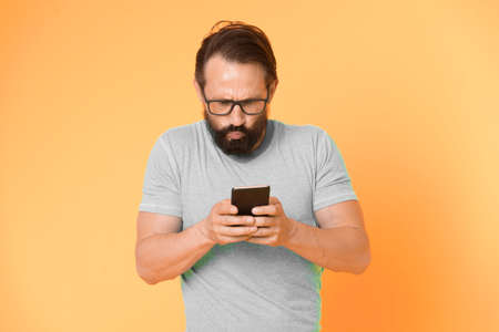 Hipster puzzled use smartphone. Man inexperienced user of modern smartphone. Stay in touch with smartphone. Join online community. User friendly concept. Man puzzled mobile phone opportunities