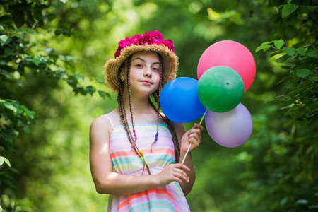 happy kid girl in straw hat with rose flowers in summer nature with party balloons, joy Foto de archivo