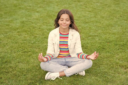 kid meditating in yoga pose on grass. child in lotus pose on green grass. Concept of calm and meditation. meditation in nature. peace and relax. small girl meditate in summer park. healthy lifestyle Stock Photo