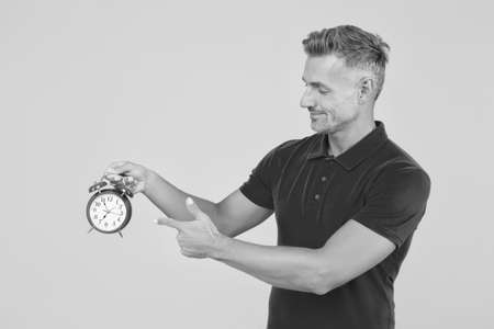 Look at clock. Handsome man point finger at alarm clock. Check current time. Countdown and deadline. Punctuality and accuracy. Temporal measurement. Chronometry and timekeeping