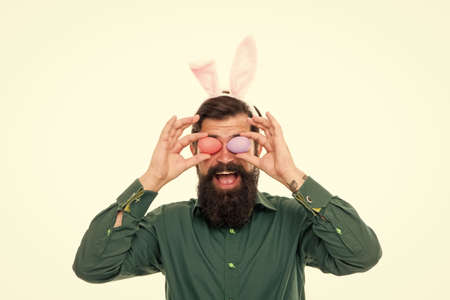 I see spring is coming. Bearded man hold eggs as glasses. Hipster wear bunny ears. Rabbit bringing eggs in spring. Spring season. Celebrating spring equinox. Holiday celebration