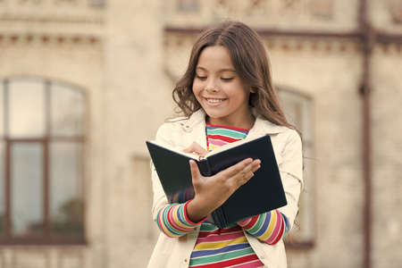 Access to much more than just book. Knowledge concept. Little girl hold book. Girl with book school building background. Book from library. Making notes. Inspired poet. Talented cute schoolgirl