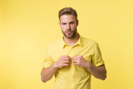 It is hot here. I will show you my body. Man handsome bearded guy undressing yellow background. Guy confident attractive macho feels while unbuttoning shirt. Want to see torso