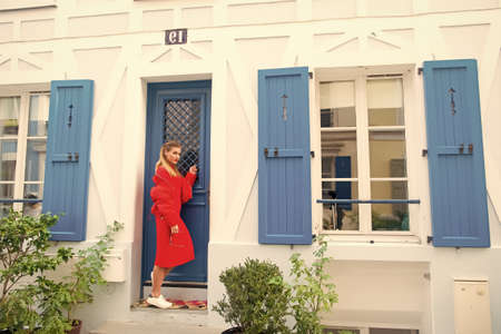Anybody home. Lady guest knocking door waits owner apartment let her enter. Woman stylish outfit stand near door entrance house picturesque street in Paris. Visiting friends on vacation or holidays Banque d'images
