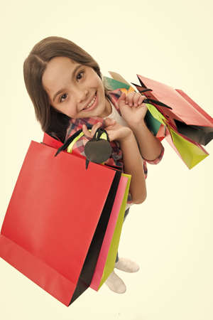 I will take it all. Kid girl happy smiling face carries bunch packages white background. Girl likes shopping on sale season. Kid happy shopping in mall. Child cute fashionista shopping