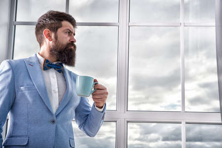 Beginning of great day. Important day in his life. Get ready. Enjoy every minute. Hipster in tuxedo with bow tie making sip of coffee. But first coffee. Man groom drinking coffee early in morning
