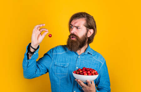 mature brutal hipster with ripe fresh cherry, fruit