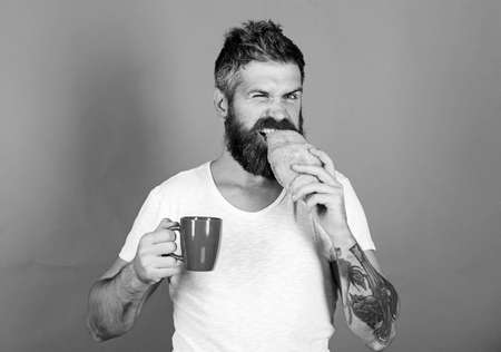 i am hungry. Perfect match. feel hunger. Bearded hipster enjoy breakfast drink coffee. Morning tradition concept. Fresh baked croissant. Delicious breakfast. Unhealthy but yummy breakfast