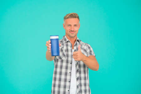 Happy guy give thumbs up hand gesture to mens gel bottle blue background copy space, approval