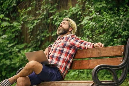 Doing research. successful entrepreneur. mature man sitting on park bench with laptop and checking email. Freelancer man working on computer. Businessman using notebook in park. Escaped of office