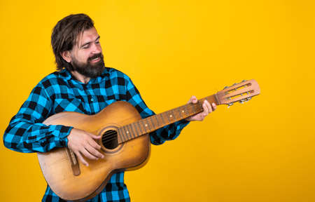 playing country music. trendy looking bearded hipster guitarist. music concept. brutal handsome man with moustache. mature guitar player. masculinity and charisma