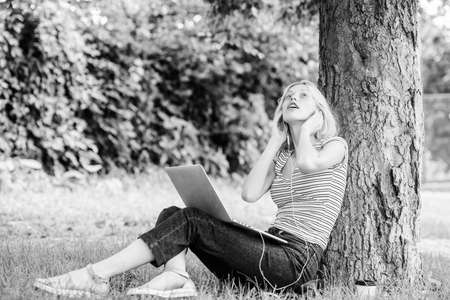 Work in summer park. Reasons why you should take your work outside. Nature is essential to wellbeing and ability to be productive and high functioning at work. Girl work with laptop in park Banque d'images