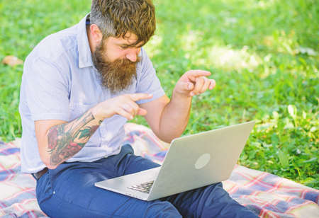 Man bearded with laptop sit meadow nature background. Writer looking for inspiration nature environment. Inspiration for blogging. Looking for inspiration. Blogger becoming inspired by nature