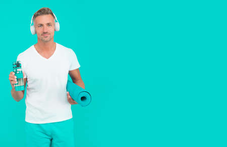 Choose sport drink wisely. Athletic man hold sport bottle and gym mat. Handsome sportsman blue background. Hydration for athletes. Sport and diet. Health and recreation. Fluids in sport, copy space