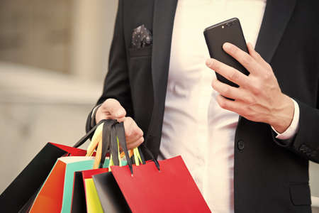 Shopping on cyber monday or black friday sale. New technology for business communication. Shopping bags and smartphone in hands of man. After day shopping. digital marketing for successful buy online
