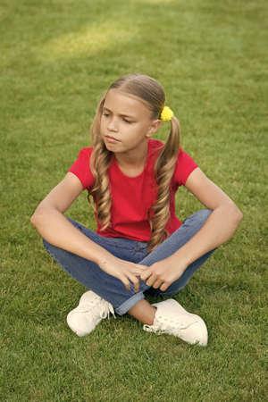 Little child sit on green grass. Little girl wear long hairstyle. Little kid in summer style. Beauty look of little baby. Kids wardrobe. Stylish trends. Trendy fashion. Hair salon
