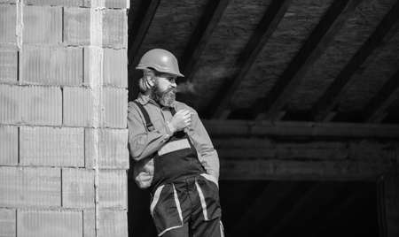 construction worker smoking cigarette. building is under construction. bearded man in uniform and hard hat. copy space. repairman engineer wear helmet on site. tired builder relax. time to relax