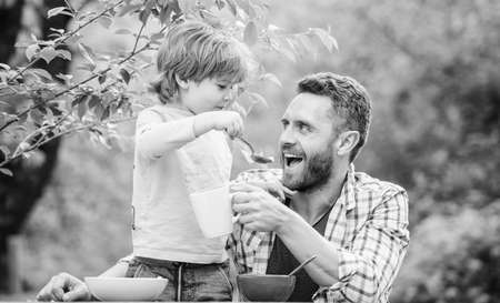 Father son eat food and have fun. Feeding baby. Menu for children. Family enjoy homemade meal. Food habits. Little boy with dad eating food nature background. Summer breakfast. Healthy food concept Stock fotó