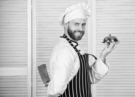 cook in restaurant, uniform. Professional in kitchen. culinary cuisine. confident man in apron and hat hold tray. chef ready for cooking. bearded man loves eating food. compliment from chef