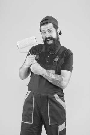 happy bearded man painter worker in boiler suit uniform using paint roller tool for painting wall into yellow color, decorator