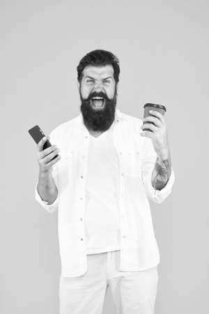 real winner. use modern technology. happy bearded man holding phone while drink coffee. brutal hipster drinking takeaway beverage. angry guy with beard and moustache has mobile phone. morning routine