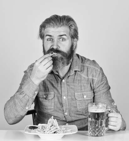 lazy man enjoying fresh beer and junk food. man with fast food. beer and french fries in restaurant. eating and drinking at bar. hipster relax in tavern. bearded guy having snack Stock fotó