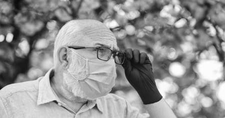 Protect and from virus infection. Limit risk infection spreading. Infection is in air. Seniors vulnerable believing misinformation about virus Senior man wearing face mask and gloves outdoors