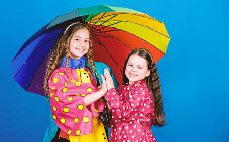 cheerful hipster children, sisterhood. family bonds. Little girls in raincoat. autumn fashion. rain protection. Rainbow. happy little girls with colorful umbrella. Feeling cold