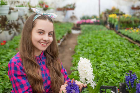 happy teen girl florist care pot plants in greenhouse, spring