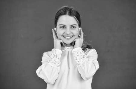 favorite tune. home schooling online education. back to school. small girl in headphone at blackboard. listening audio book. free ebook. cool girl in headphones listening to music. e-learning concept
