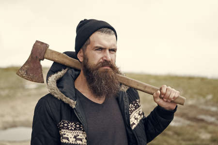 bearded handsome serious man with rusty axe on mountain top Stock Photo