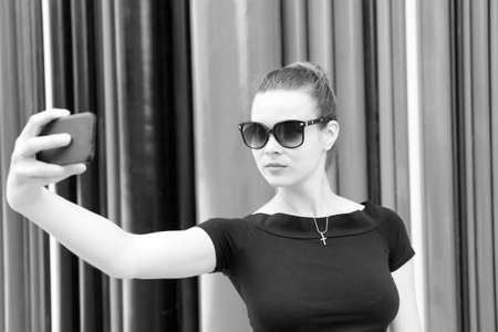 Woman make selfie with smartphone in paris, france. Woman with mobile phone on colorful background. Girl in sunglasses with fashion look and sensual beauty. New technology and modern life