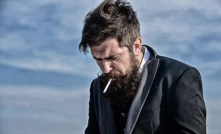 Lighting up cigarette. Businessman against the sky. Future success. Male formal fashion. Bearded man smoking cigarette. smoke. brutal caucasian hipster with moustache. Mature hipster with beard