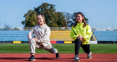 Active children in activewear stand in lunge position at athletics stadium, childrens sports school Standard-Bild