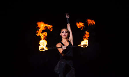 Fire and sparks. Sexy woman twirl burning stick in darkness. Fire performance. Baton twirling. Juggling devil stick. Night party. Outdoor festival. Holiday celebration