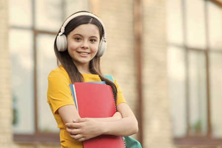 Learning foreign language. Small girl learn English. Little child hold English books. Listening comprehension skills. English literature. English grammar. Private lesson. Welcome to language school