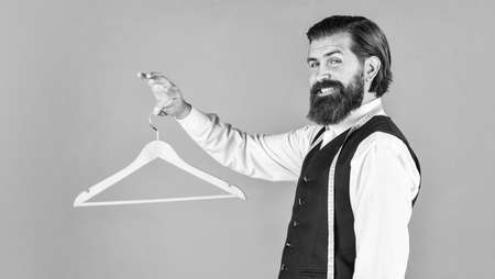 portrait of man holding hanger. tailor man use tape measure. professional male sartor with measuring tape and hanger. Handsome man in smart casual wear is holding hanger