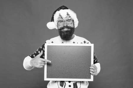 Presentation announcement. Promoting winter goods. Profitable offer here. Rental services. Winter price drop. Bearded hipster Santa claus. Joyful man show blackboard copy space. Happy winter holidays