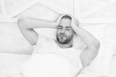 Limit naps. early morning wakeup. man sleeping white bedroom. cosy weekend at home. time to relax. guy had sleepless night. male health concept. Peacefulness concept. tired man sleep in bed Zdjęcie Seryjne