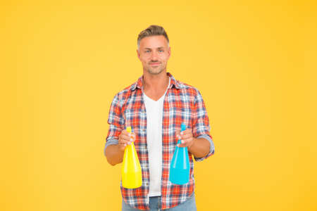Cleaning solution. Happy guy hold spray bottles. Cleaning man yellow background. Cleaning service. Using spray disinfectants. Disinfecting home. Domestic cleaning. Household cleaners Stock Photo