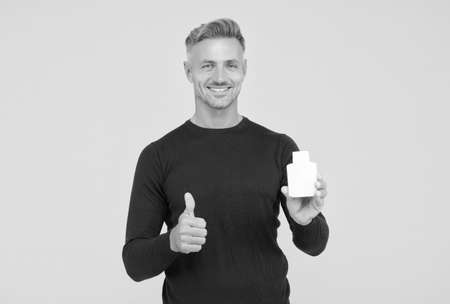 Happy caucasian man with unshaven facial hair in casual style show thumbs ups hand gesture holding mens lotion to keep skin healthy yellow background, best