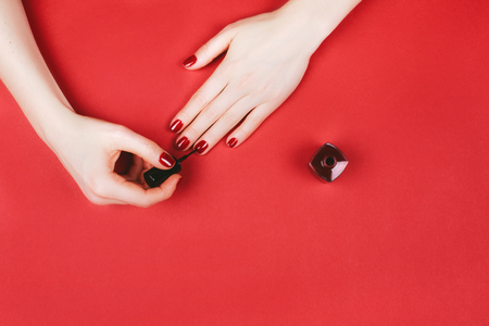 Woman making manicure by herself on marsala background.
